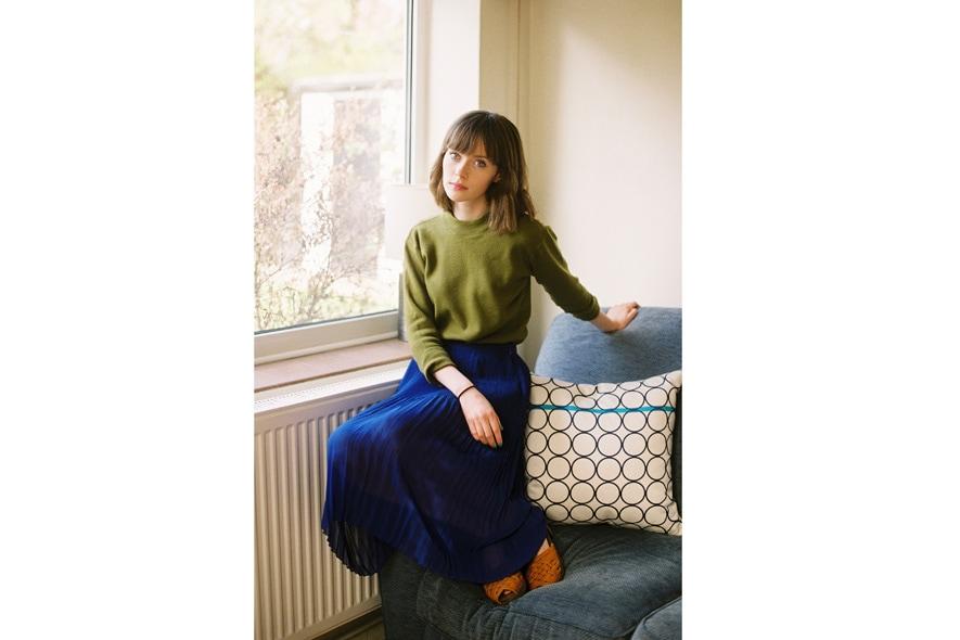 Claire Healy con maglioncino verde e gonna plissè blu e clogs