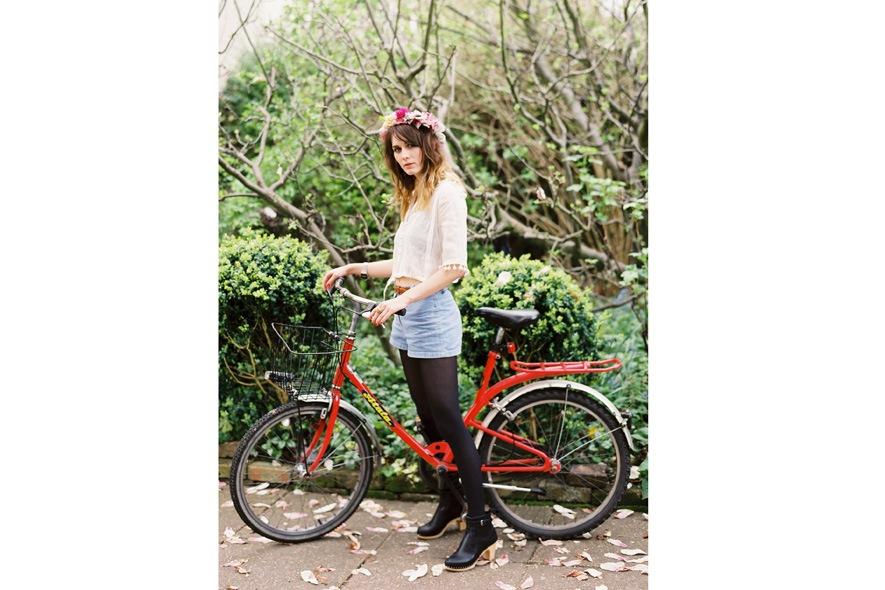 Cara Dawson con camicia bianca e shorts di jeans in bicicletta 2