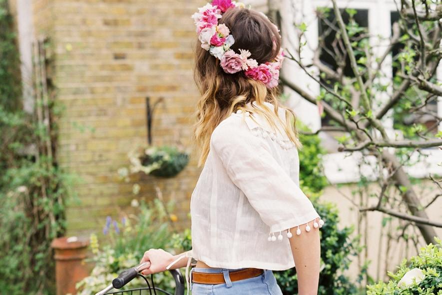 Cara Dawson con camicia bianca e shorts di jeans in bicicletta
