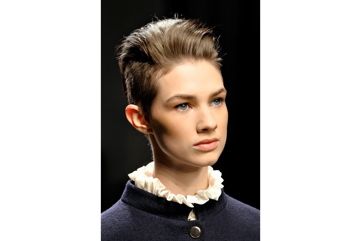 Capelli corti di lato e super ciuffo sulla testa è la scelta di Karen Walker