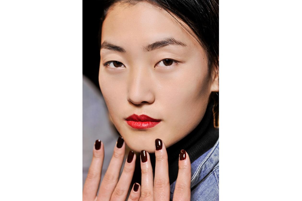 Dark brown sulle mani della modella di Tadashi Shoji