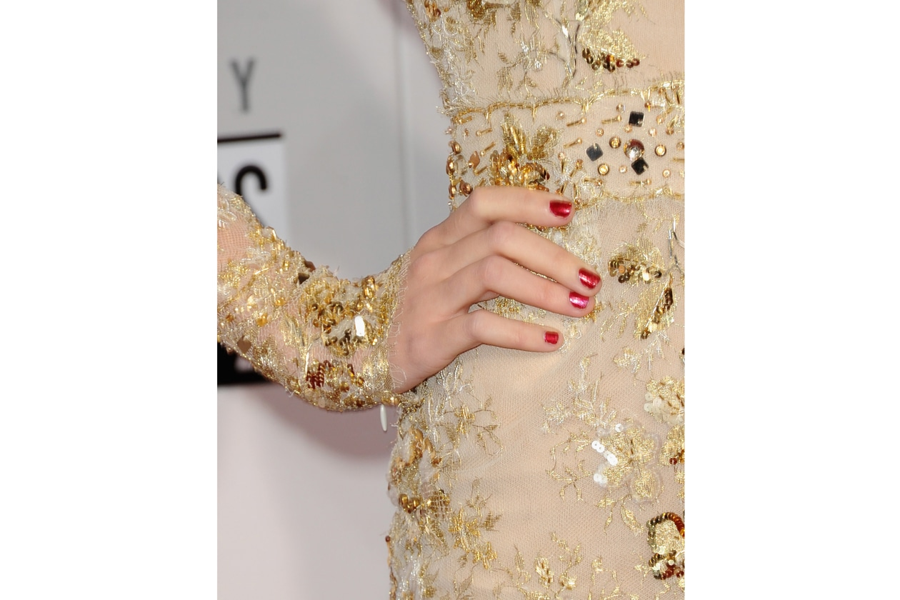 Taylor Swift è stata fotografata con un rosso carminio shimmer, una nuance molto bella ma su una manicure non proprio perfetta