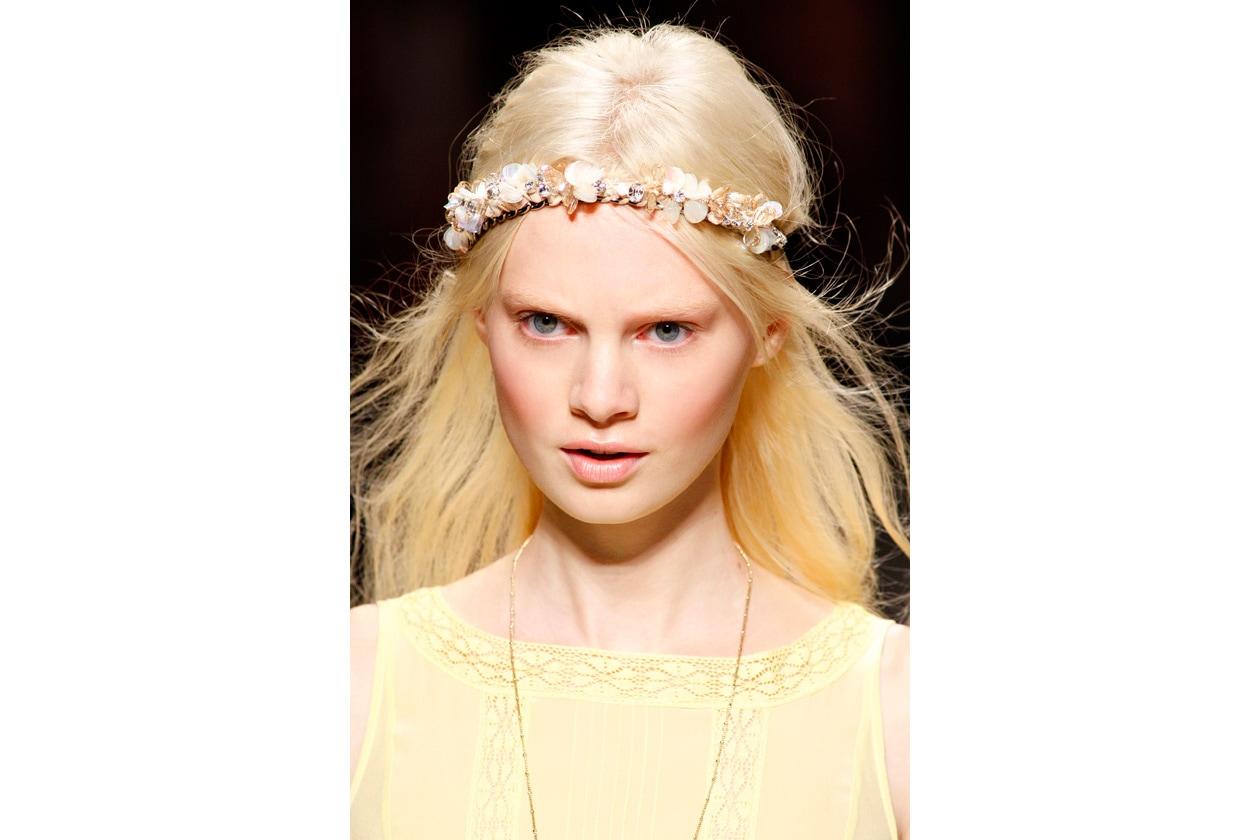 Capello sciolto impreziosito da un cerchietto di fiori che trasforma la donna in dea dell'amore (Blugirl)