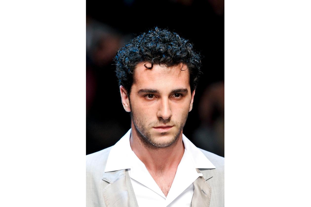 Una chioma morbida incornicia il volto dai tratti mediterranei del modello di Dolce&Gabbana