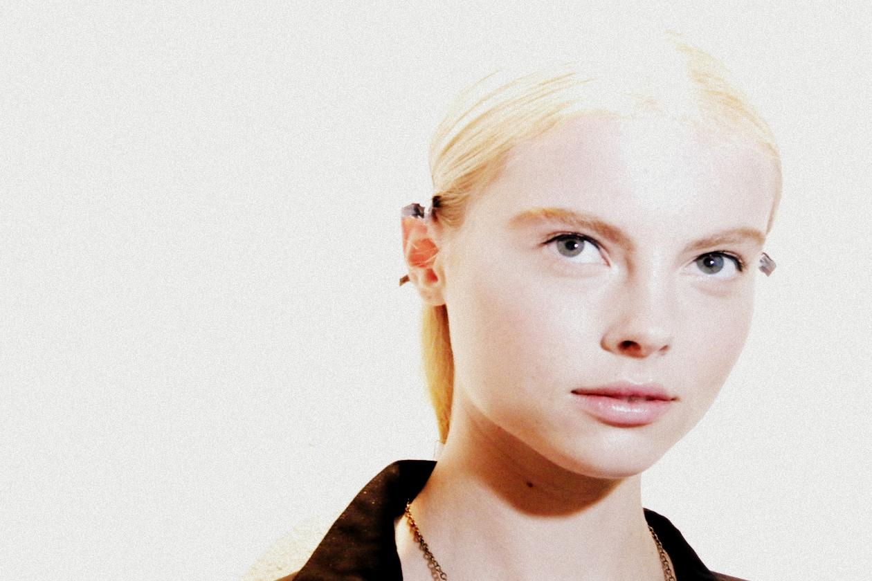 Se il trucco è nude, il blush scolpisce gli zigomi con bagliori di luce che si diffonde anche sulle tempie e sui contorni del viso (Blumarine)