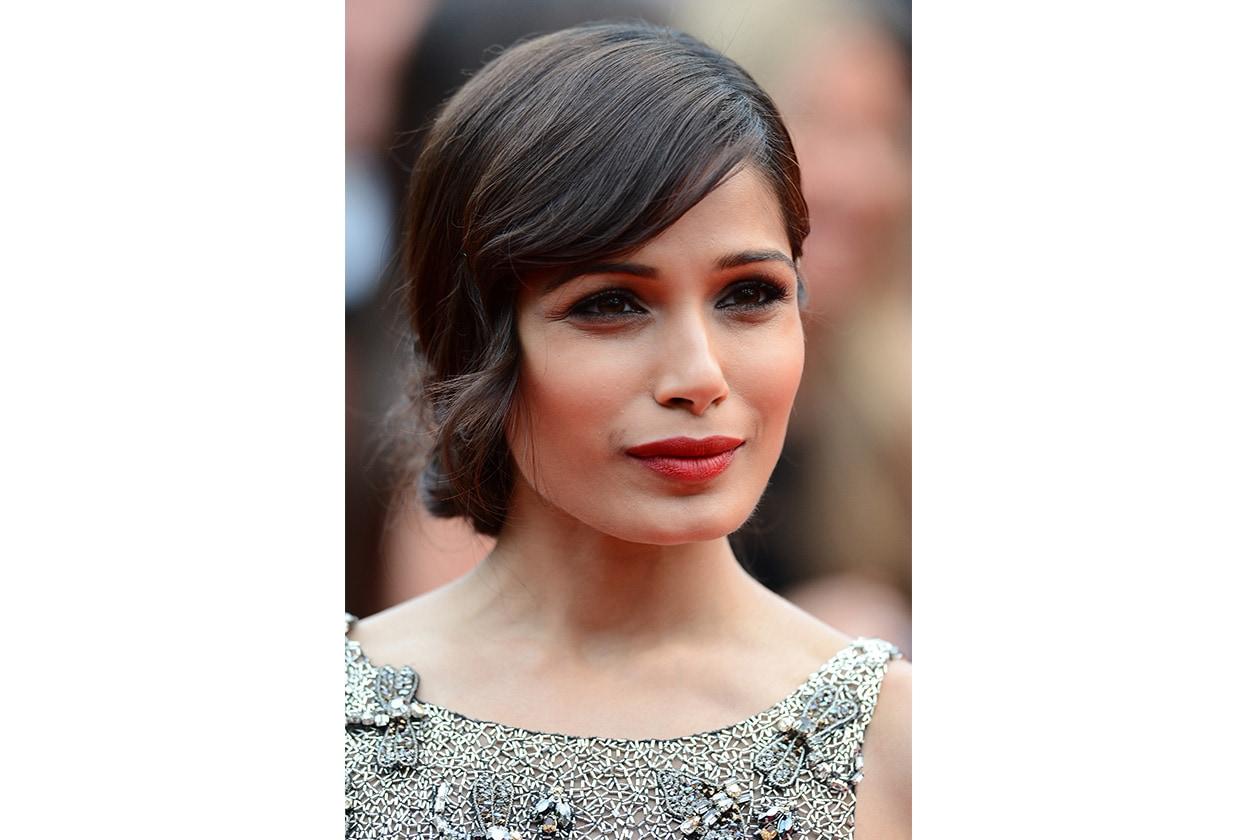Frieda Pinto copre il viso con un ciuffo neoromantico a sottolineare lo sguardo dolce che la caratterizza