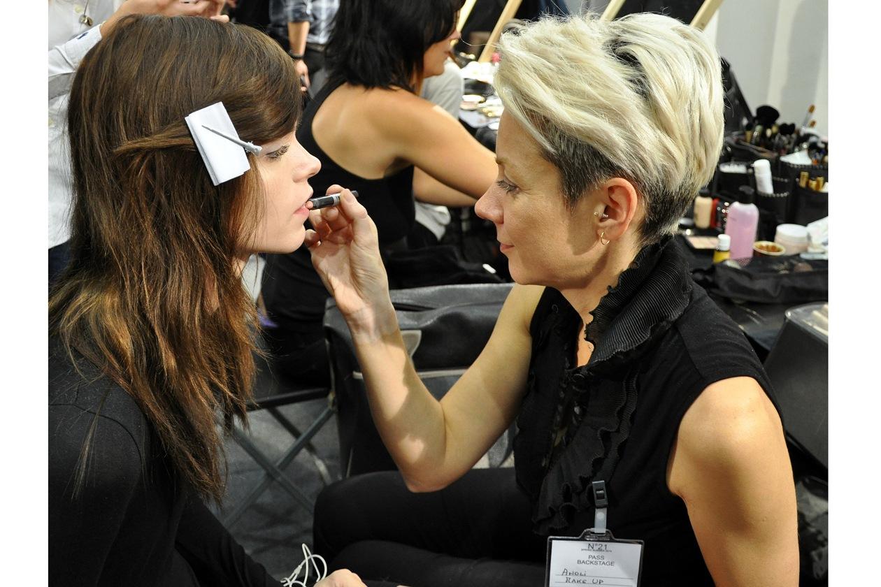 Una truccatrice del team MAC colora le labbra della modella Meghan Collinson. La nuance scelta? Un rosa naturale leggermente opaco