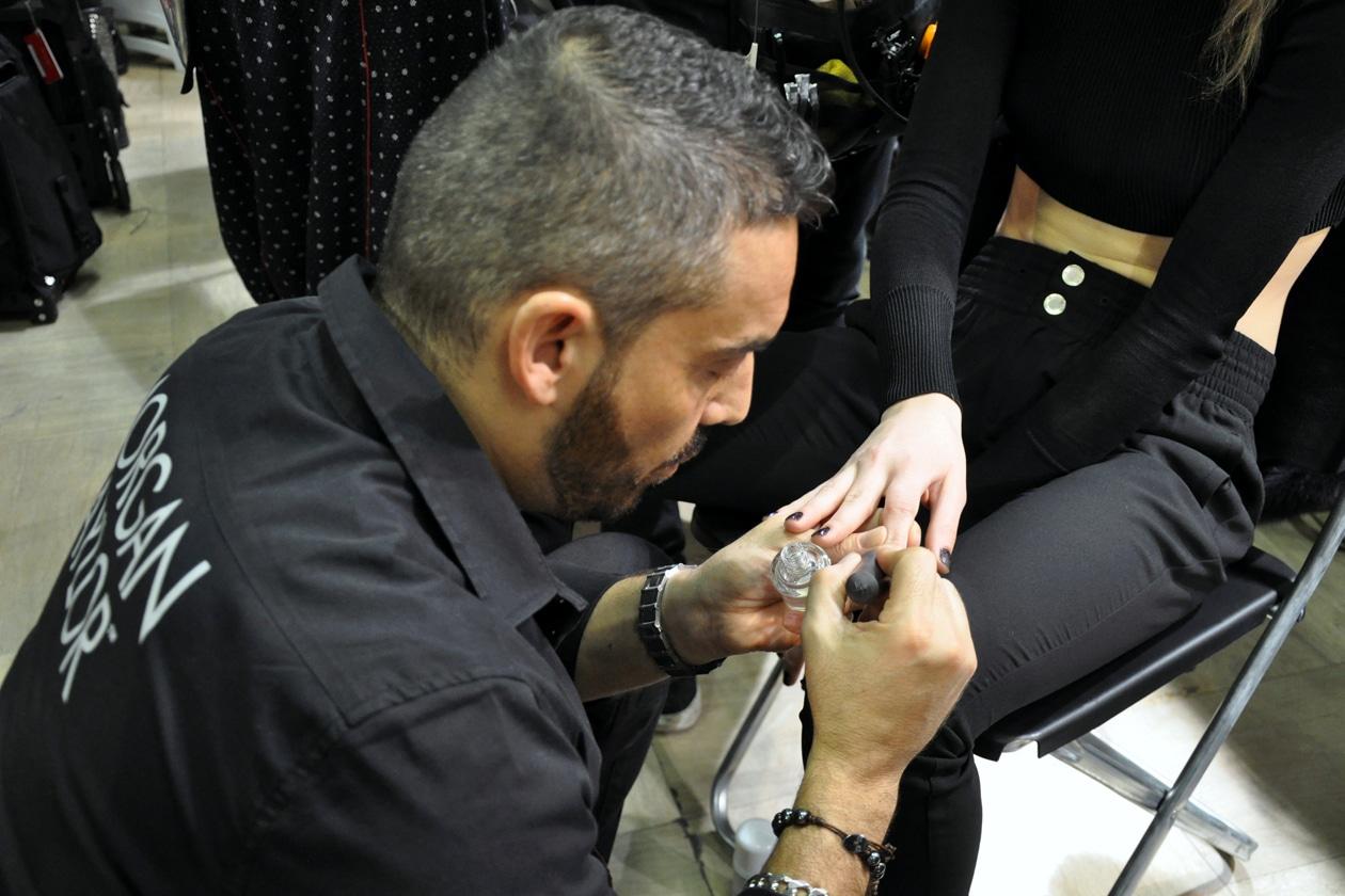 Antonio Sacripante, CEO dell'Accademia nazionale di nail art Nails&Beauty, mentre applica lo smalto sulle unghie della modella