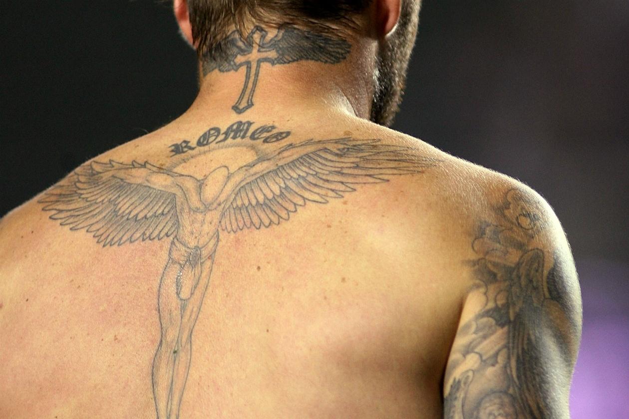 Sul collo ha una croce alata e sotto un angelo con il nome del figlio Romeo