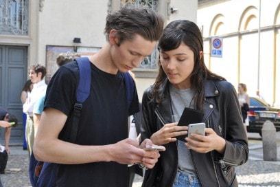Tendenze capelli dallo street style a Milano: hair look spettinato per lui, effetto wet per lei