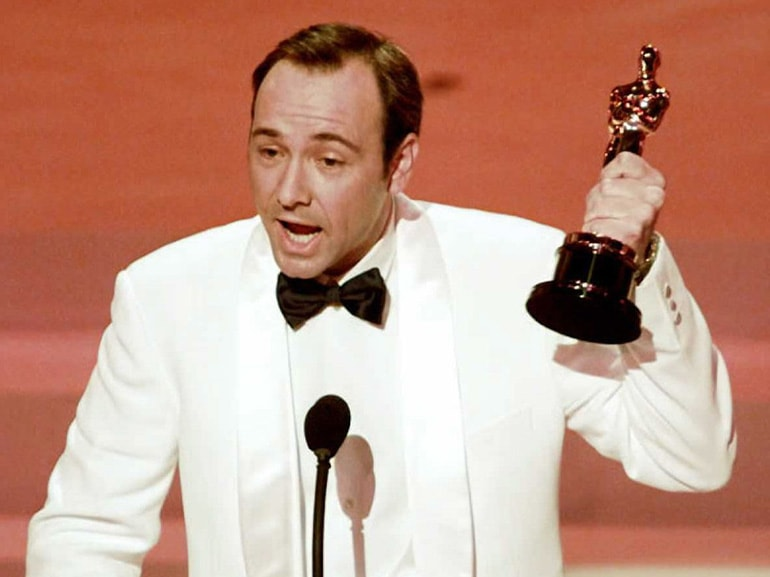 Kevin Spacey holds up his Oscar after winning Best