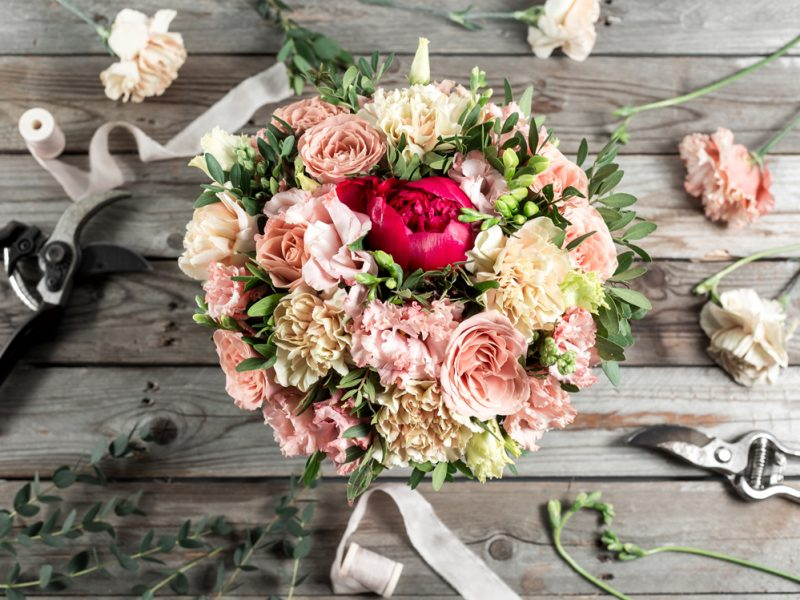 The florist desktop with working tools on gray old wooden background