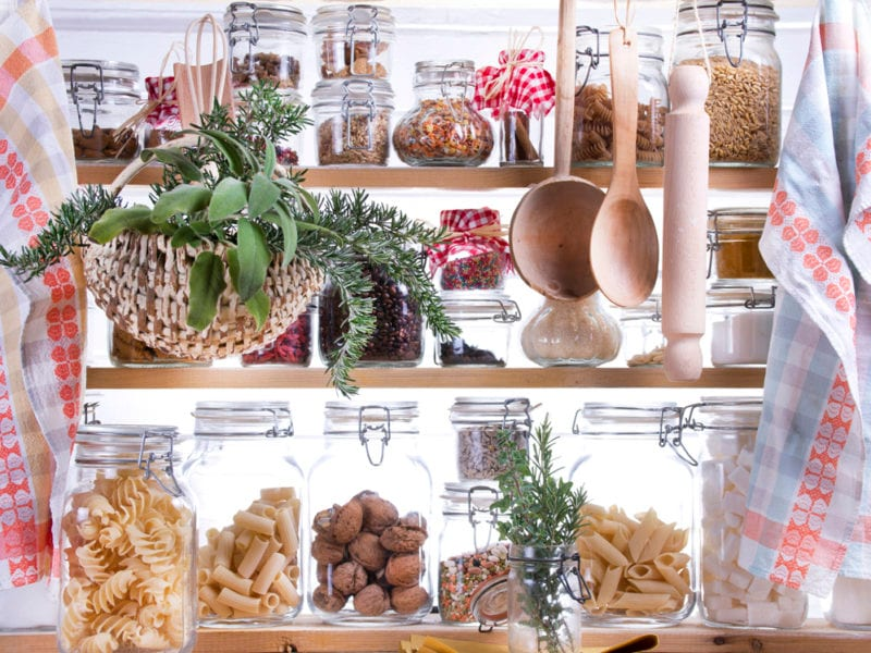 Dried foods stored in glass jars within a small pantry
