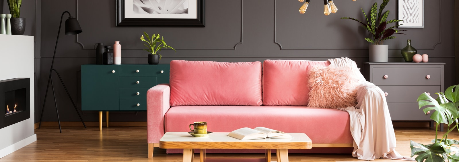 Wooden coffee table with tea cup and open book standing on carpet in dark living room interior with powder pink lounge with fur cushion and blanket