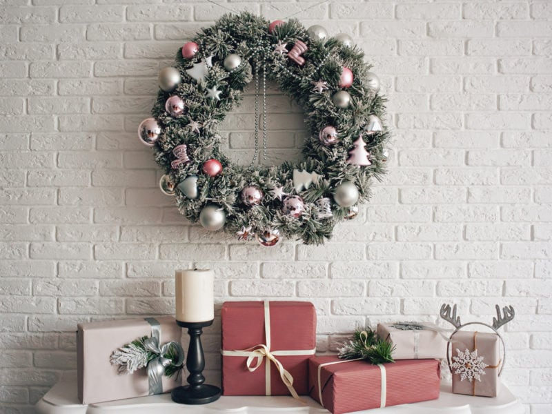 A traditional bright Christmas wreath hanging over the fireplace, on a white brick wall, and packaged gifts are stacked on a fireplace with candles.