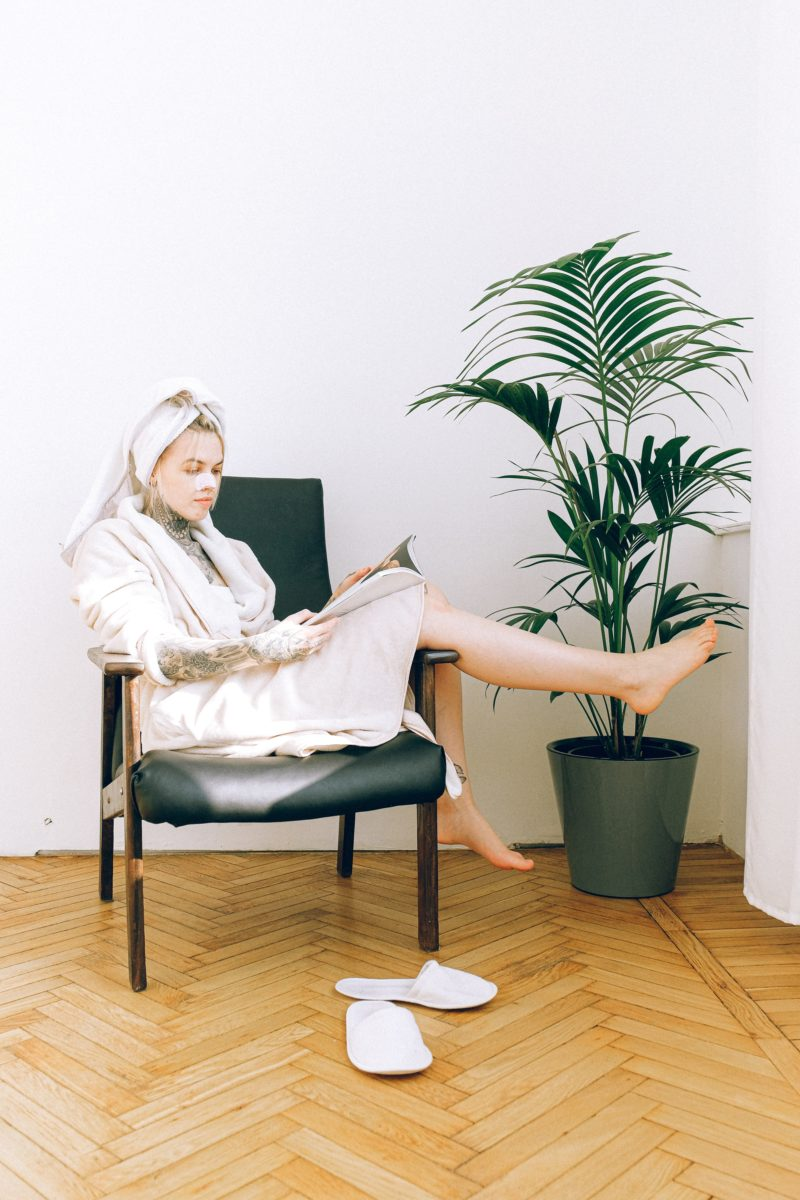 woman-in-white-long-sleeve-shirt-sitting-on-black-chair-3852037