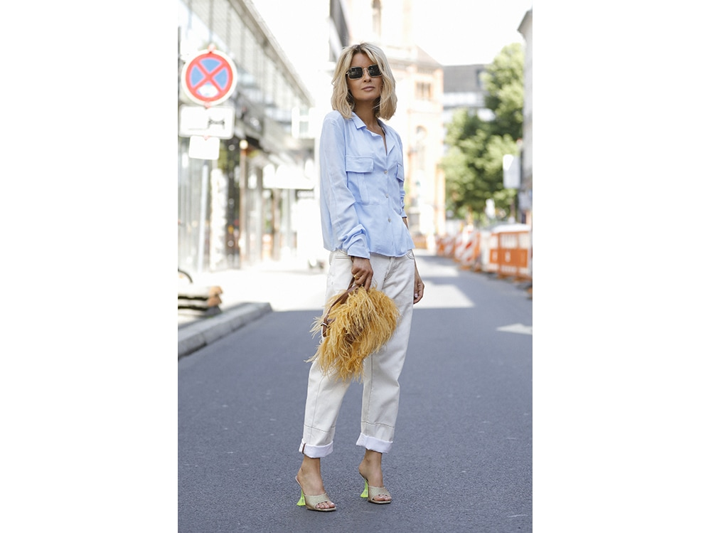 Influencer-Gitta-Banko-wearing-a-light-blue-blouse-by-Zara,-a-white-jeans-by-Marni,-a-yellow-feather-bag-by-Marquez-Almeida,-glitter-mules-with-green-heels-by-Amina-Muaddi-and-sunglasses-by-Ray-Ban