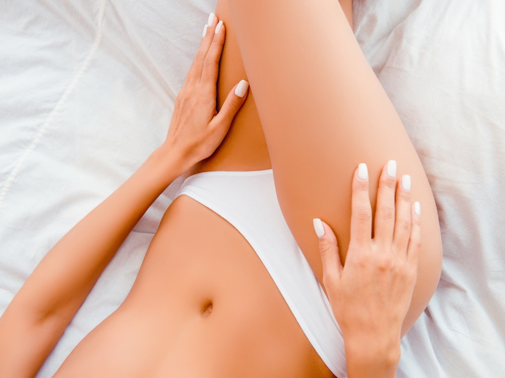 Close up of slim fit woman in white drawers lying on bed